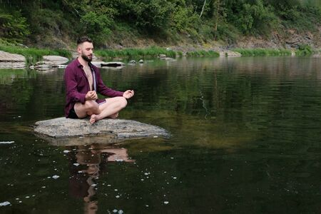A guy with a kakvkazskoy appearance in a shirt with long sleeves sits on a stone in a river or lake. The concept of yoga in the forest, relaxation in the mountains, travel and lifestyle. Copy space..