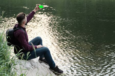 A guy with a phone in his hands sits on a stone by the river. Traveler with a backpack and a smartphone makes selfie or shooting online. Concept of travel, tourism and lifestyle. Copy space.