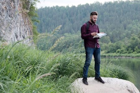 A bearded guy in jeans and a t-shirt with a map in his hands is standing on a stone on the bank of a mountain river against the background of the forest. Concept of tourism, travel and lifestyle.