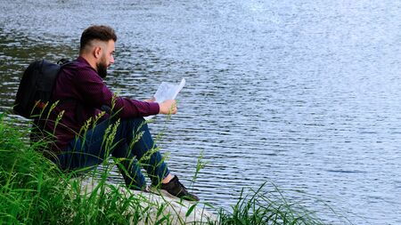 A traveler with a backpack holds a map and thoughtfully looks far ahead. The guy in jeans and a shirt sits on a stone by the river. Concept of travel, tourism, planning a path and lifestyle.Copy space