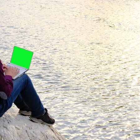 Traveler working on a laptop. A man in jeans and sneakers sits on a stone by a river, lake or sea. Concept for travel, tourism, freelancing and lifestyle. Mock-up blank. Copy space.