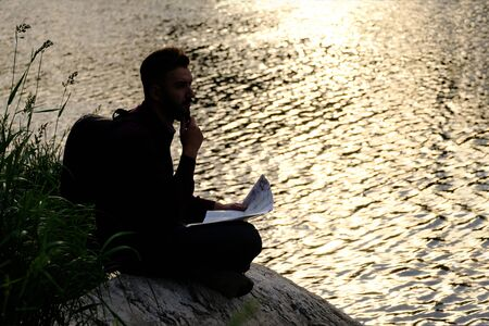 A traveler with a backpack holds a map and thoughtfully looks ahead. The silhouette of a guy sitting on a stone by the river and touching his beard. Concept of planning a path and lifestyle.Copy space Banco de Imagens
