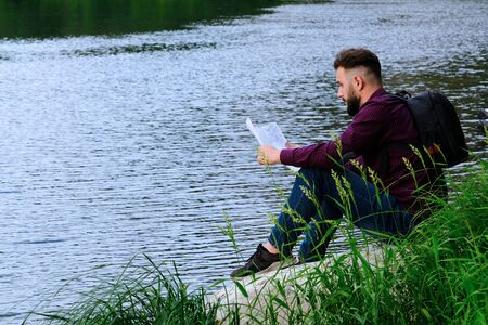 The traveler with a backpack holds a map in his hands and thoughtfully looks far ahead. The guy sits on a stone by the river. Concept of travel, tourism, planning a path and lifestyle. Copy space.