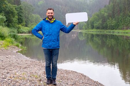 A funny young man in a jacket is smiling and holding a white sign in his hand. The guy on the bank of a mountain river in the forest. Template for advertising demi-season clothing or tourism. Mock-up.