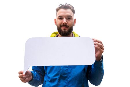 A funny young man with a beard is smiling and holding a white sign in his hands. The guy in the blue jacket is isolated on a white. Template for advertising autumn clothes or discounts on travel.