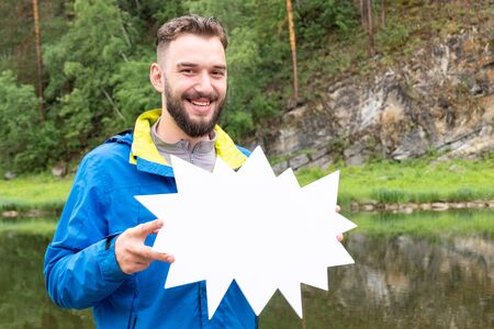 A funny young man with a beard is smiling and holding a white sign.The guy in the blue jacket in nature in the mountains near the river.Template for advertising or discounts autumn clothes or tourism.