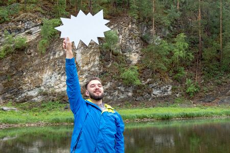 Seasonal discounts for autumn clothes and tourism. The guy in the blue jacket in nature in the mountains near the river. A funny young man with a beard is smiling and holding up a white sign.