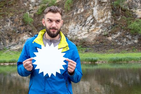 Funny guy tourist with a beard slyly looks to the side and holds a white sign.Season of discounts for autumn clothes for travel.Young man in a blue jacket on the nature in the mountains near the river