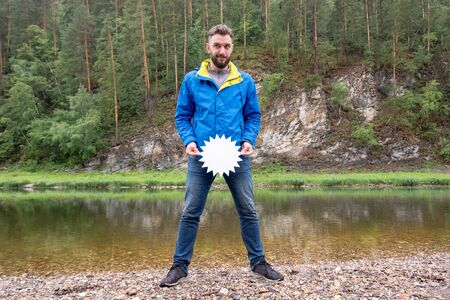 Season of discounts for autumn clothes for travel. A funny tourist guy with a beard slyly looks to the side and holds a white star-shaped plate at the waist level. Young man in a blue jacket on the nature in the mountains near the river.