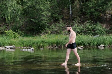 Brutal Brunette Caucasian-looking guy with a beard is walking on the surface of the water in a river or a lake in the forest. The concept of human unity with nature, travel and lifestyle. Copy space.