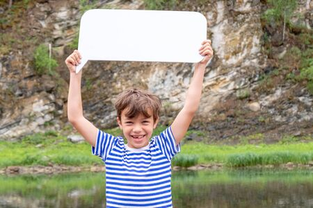 Cheerful boy in a striped T-shirt like a sailor holding a sign over his head. The teenager laughs and advertises something in the mountains. Discounts and promotions, travel and camping in nature. Seasonal concept.
