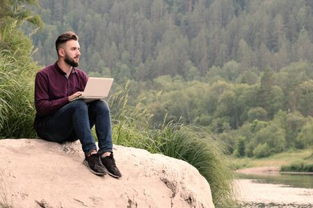 A bearded guy working on a white laptop sitting on a stone on the bank of a mountain river against the background of the forest. The concept of freelance, travel, tourism and lifestyle. Copy space.