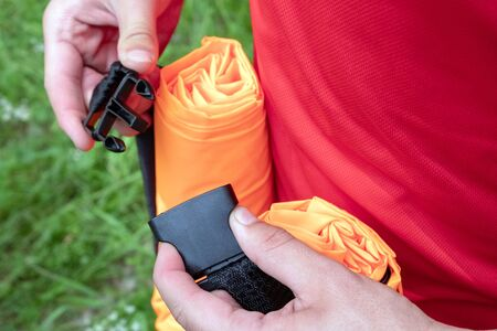 Mens hands fasten or unfasten a semi-automatic fastener for connecting fabric tapes, lines, belts. Fastex on the orange inflatable sofa Lamzac. Close-up.
