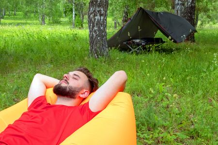 . Traveler resting in nature in the forest. The guy in the red T-shirt lies with his eyes closed on the orange inflatable Lamzatz sofa Camping tent in the background. Stock Photo