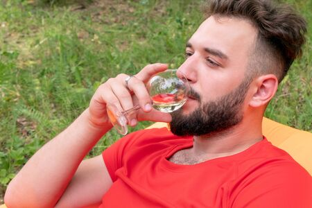 Caucasian traveler on vacation in the woods uses alcohol. Brutal guy with a beard in a red T-shirt drinks wine. Close-up. Portrait of a handsome young man.