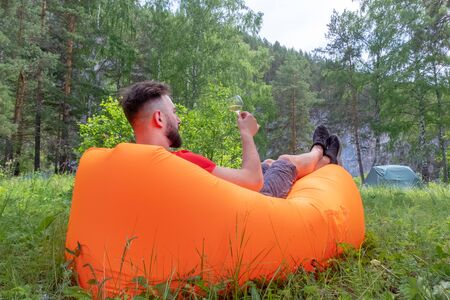 The guy with the beard in the red T-shirt lies on the orange inflatable Lamzatz sofa and looks at the glass with a white alcoholic drink. Caucasian traveler drinks wine at a picnic resting in the mountains. Tent in the background. Stock Photo