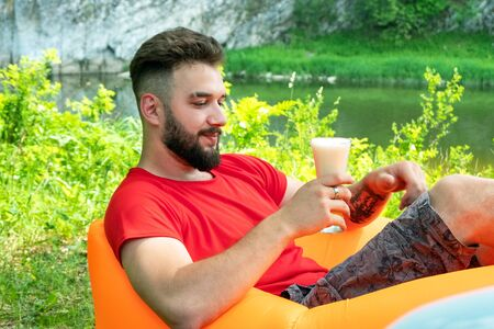 The traveler with the beard in a red T-shirt lies on Lamzac orange inflatable sofa and holds a glass of beer in his hand. Caucasian guy on vacation in the forest on the bank of a mountain river.