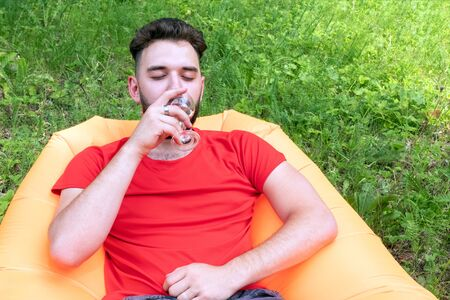 Caucasian traveler drinks wine at a picnic resting in the forest.A guy with a beard in a red T-shirt is lying on an orange inflatable Lamzatz sofa.