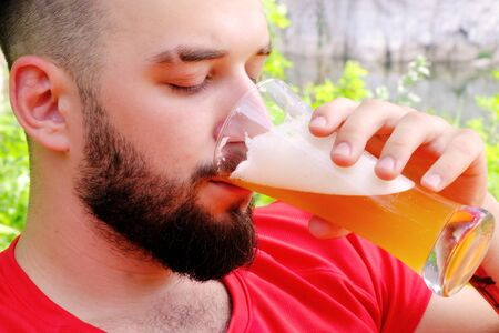 Brutal guy with a beard in a red T-shirt drinks beer. Caucasian traveler on vacation in the woods uses alcohol. Close-up. Portrait of a handsome young man.