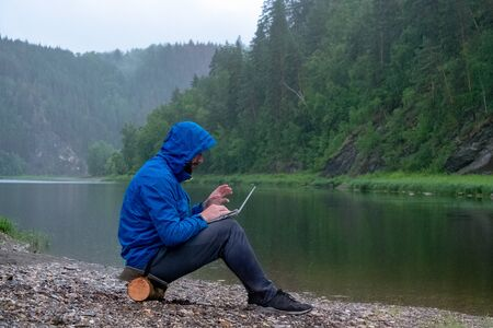 The guy in the blue jacket with a hood work on the laptop in and sits on the bank of the river in the rain. Bad weather on the moauntains. Traveler, geologist or tourist with waterproof IT equipment. Stockfoto