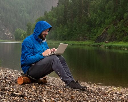 A contented bearded guy in a blue jacket with a hood sits on the bank of a river in the rain with a laptop in his lap. Freelancer Traveler, geologist or tourist in the mountains with modern waterproof IT equipment. Bad weather.