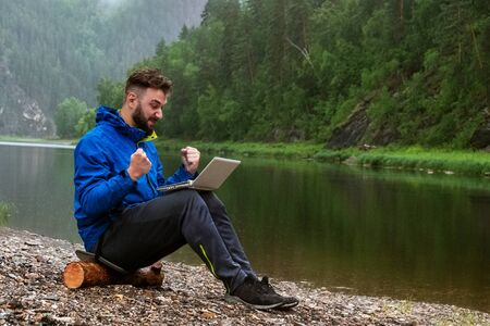 Successful electronic transaction in the rain. A bearded guy in a blue jacket working on a laptop on the river bank. Freelancer traveler, geologist or tourist in bad weather in the mountains with modern water-protective IT equipment.