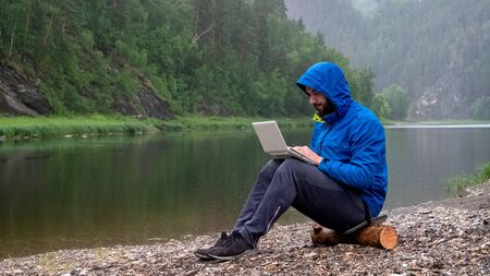 A man in a blue jacket with a hood is working on a white laptop while sitting on a log in the rain by the river. Concept waterproof computer equipment. Programmer or Hacker in the mountains. Stock Photo