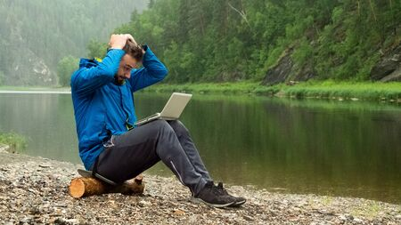 A guy in a blue jacket with a white laptop is sitting on a log in the rain on the bank of the river and holding his head. Conceptual error in programming or disruption of a business transaction. Programmer or Hacker in the mountains and waterproof computer equipment.