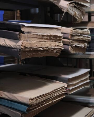 Old battered documents or newspaper files or large books on the bookshelves in the library or archive room. The concept of historical value and obtaining knowledge. Selective focus. Copy space background. Stock Photo
