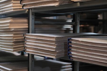 Bookshelves in the old library or museum archive room. Blurred background. Selective focus. Bundles of documents or filing of newspapers. The concept of historical value and the desire for knowledge. Basement light in the book depository. Stock Photo