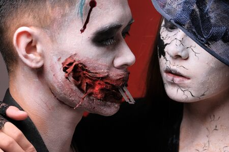 Halloween make-up style. The guy and the girl look at each other. Joker with a blade in the mouth. Close-up. Red background.