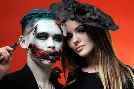 Portrait of a couple in halloween makeup style. The guy with the knife in the image of the joker and a beautiful girl in a hat like a witch. Bloody mouth with a razor blade and a seven-peak playing card in the forehead. Close-up. To advertise a makeup master or party poster for All Saints Day. Stok Fotoğraf