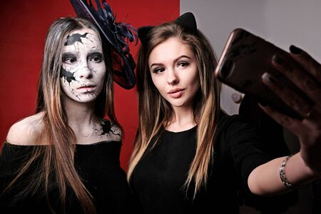 Two girls make selfies before a party on All Saints Day. Halloween makeup. The image of a cracked doll.