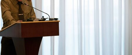 Abstract man in a green shirt stands on the podium in front of a microphone. Concept speech of a military official, the Minister of Defense or emergency situations. Close-up. Copy space.