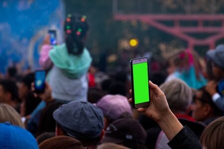 A female hand with a smartphone records or broadcasts a live concert among a crowd of fans. A blank for embedding any image instead of a green screen. Video and photography on a mobile phone as a template, mock-up. Stock Photo