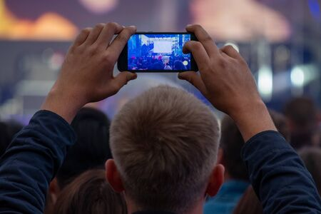 A man holds a smartphone in his hands and records or broadcasts a live street concert among a crowd of fans. he view from the back. Video and photography on a mobile phone as a template, mock-up.