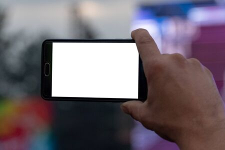 Video and photography on a mobile phone. Smartphone in a mans hand. White screen as a template, mock-up. Blank for embedding any image. Close-up.