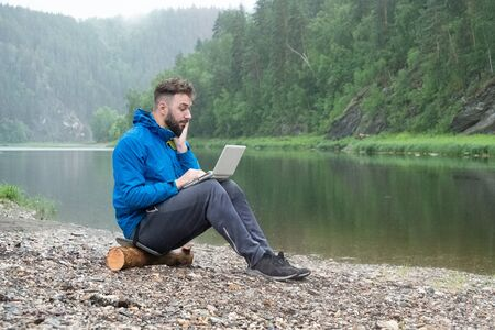 A guy in a blue jacket sits on a log near a mountain river with a laptop on his knees in the rain. A bearded young man looks in surprise at the screen of a waterproof computer. Businessman or freelancer in nature.