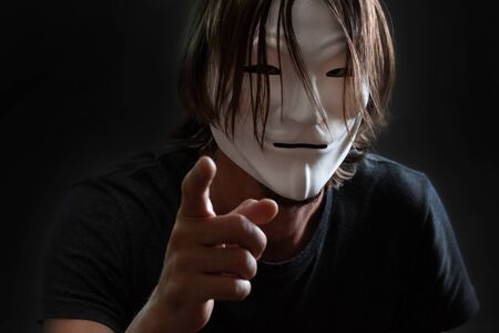 A man with long hair in a hacker or anonymous mask in a T-shirt stands with his finger forward. Gray dark background. Concept of Internet hacking or the mystery of cybercriminals.