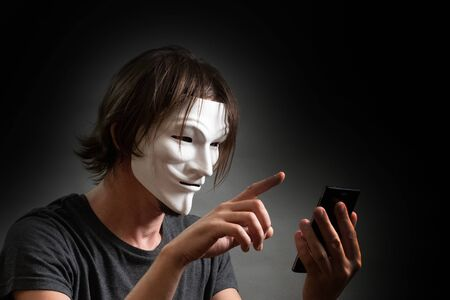 A man with long hair in a hacker or anonymous mask in a T-shirt is holding a mobile phone in his hands. The concept of an Internet hacking site, personal data or the secret of cybercriminals. Gray dark background.