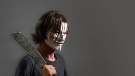 A man in a hacker or anonymous mask holds a machete on his shoulder. Halloween style. Copy space. The guy the villain with long hair, dressed in a T-shirt is standing in profile on a gray background.