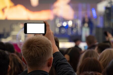A man is holding a smartphone in his hands and is recording or live broadcasting a street concert among a crowd of fans. View from the back. A blank for embedding any image instead of a white screen. Video and photography on a mobile phone as a template, mock-up.
