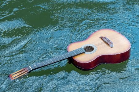 Acoustic guitar floats in the water. The concept of flood, shipwreck, tragedy of musicians in nature. Copy space. Stock Photo