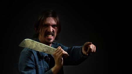 A man holds a machete on his shoulder and points the finger of his other hand forward. The guy is villainous like a Mexican or Italian with long hair, dressed in a jacket with evil emotions on face.