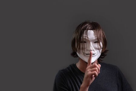 A man with long hair in a hacker or anonymous mask in a T-shirt holds a finger near his lips. The concept of silence and keeping secrets or the secret of cybercriminals. Copy space. Gray background.