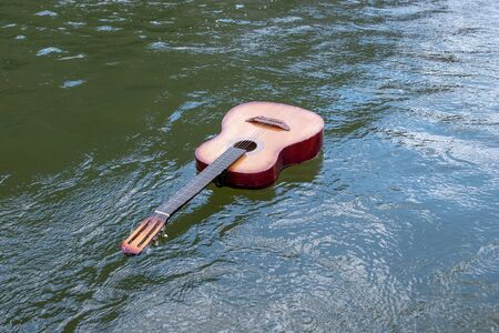 Music does not sink. An acoustic guitar floats in a river, lake or other body of water. Copy space. The concept of shipwreck, flood, tragedy of musicians in nature. 版權商用圖片