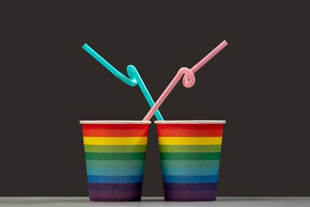 Two glasses of LGBT color with pink and blue cocktail tubes. Gray background. The concept of unification and love of people of a gay orientation or a symbol of a celebratory drink in a cafe. Isolate Selective focus. Copy space.
