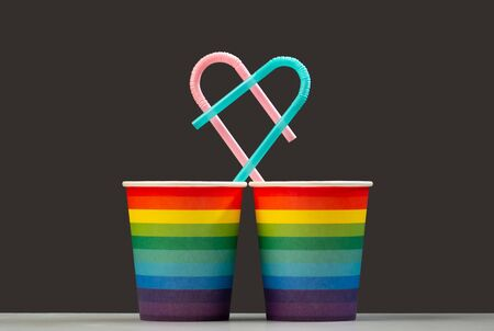 Together forever. Two LGBT color paper cups with pink and blue heart shaped cocktail tubes. The concept of unification and love of people of homosexuality or a symbol of the holiday and anniversary of living together. Gray and rainbow background. Isolate Stock Photo