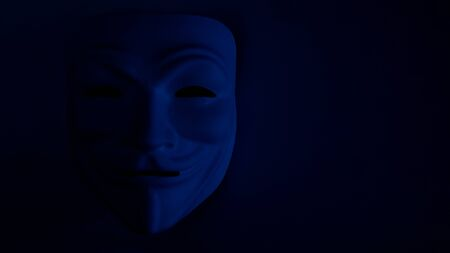 Poorly visible mask on a dark background in blue. An anonymous hacker or halloween party symbol. Monitor desktop wallpaper. Copy space. Shooting a subject in a dark key. The effect of film grain.