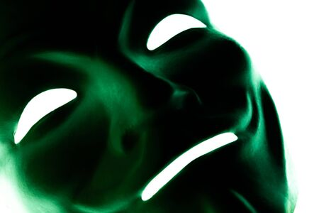 Dark green mask isolated on white. Close-up. Smile symbol of an anonymous hacker. Shooting a subject in a dark key.